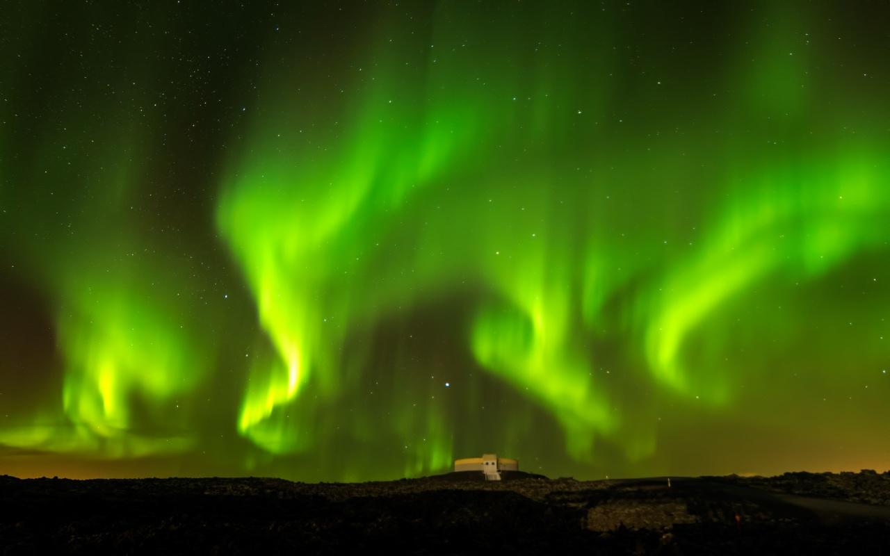 Snakes of the aurora borealis wind across the starry skies of Reykjavík.