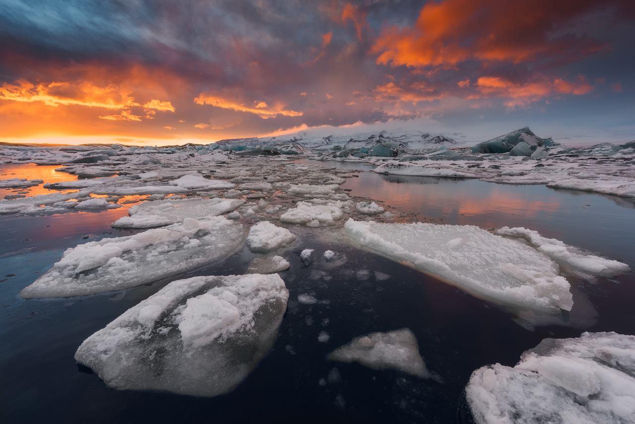 Great icebergs break from Breiðamerkurjökull glacier, falling into Jökulsárlón glacier lagoon to tranquilly drift towards the open sea.