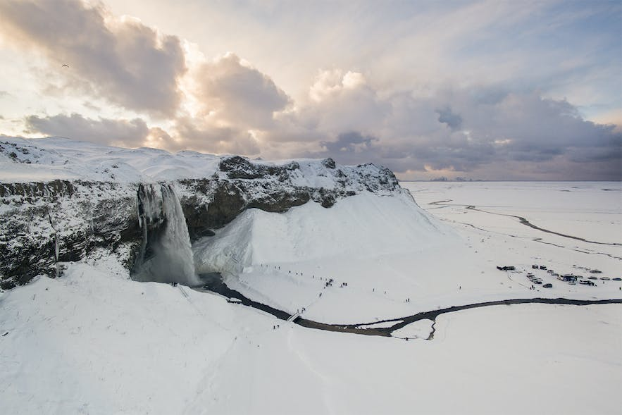 Seljalandsfoss waterfall surrounded by metres upon metres of snow.