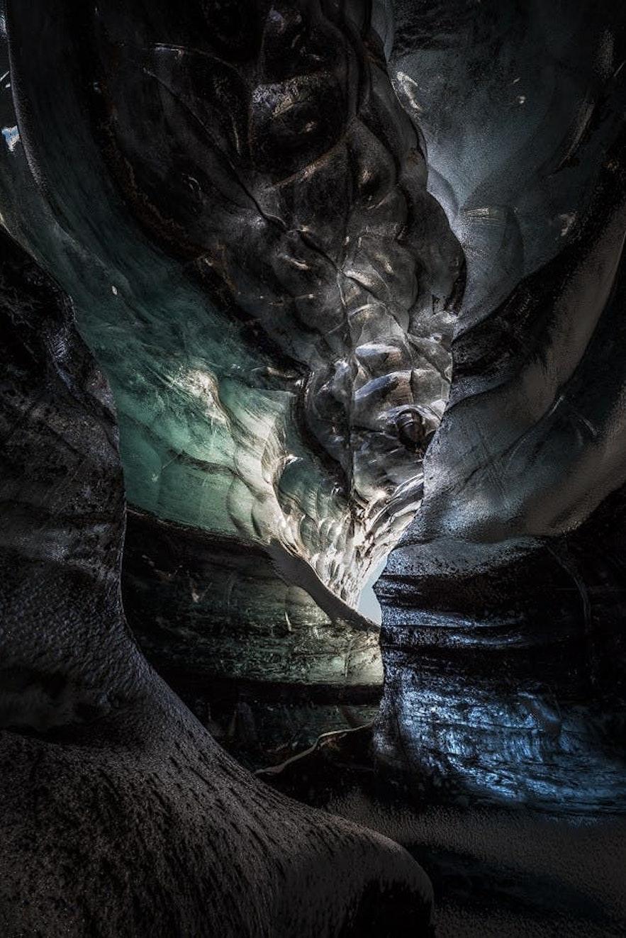 青い氷と黒い堆積物の層が交じり合うカトラの洞窟
