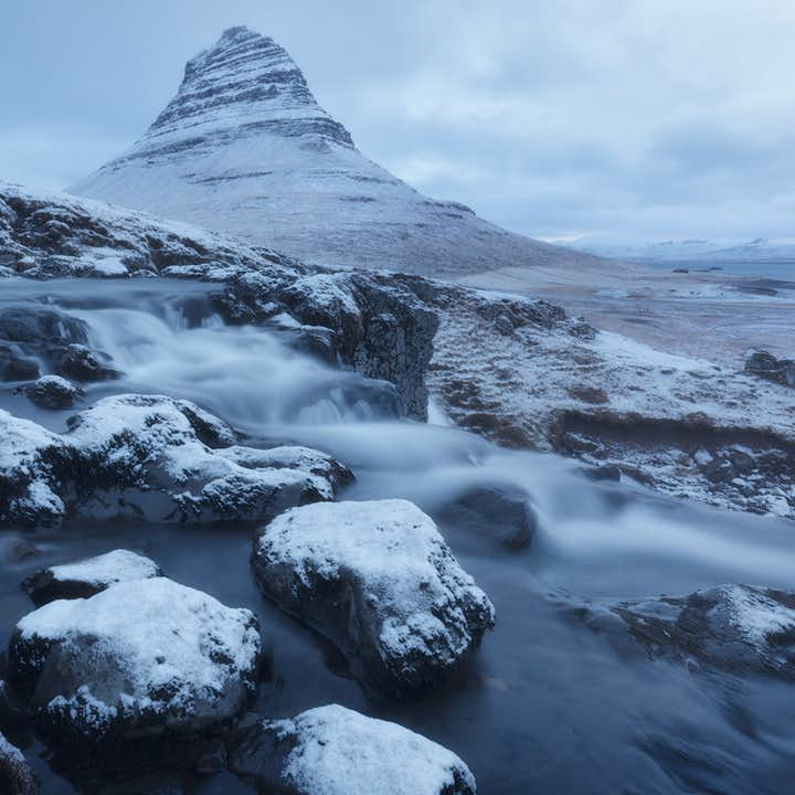 Mt. Kirkjufell, standing by the Snæfellsnes peninsula, takes on a striking look covered with snow during the Icelandic winter.