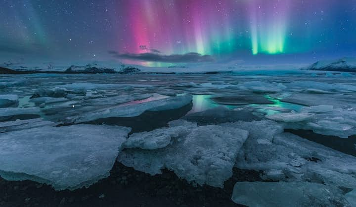 Blue northern lights dancing with purple shades over South Iceland's Jökulsárlón glacier lagoon in winter.