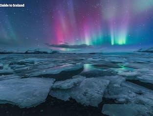 Zorza polarna tańczy zimą w fioletowych odcieniach nad laguną lodowcową Jökulsárlón w południowej Islandii.