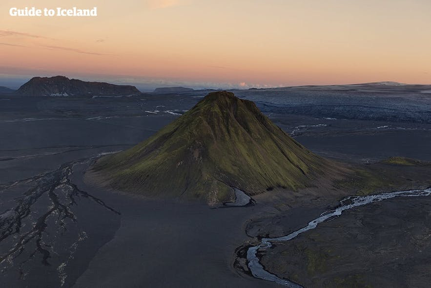 Ein einzelnstehender, von schwarzem Sand umgebener Berg im isländischen Hochland