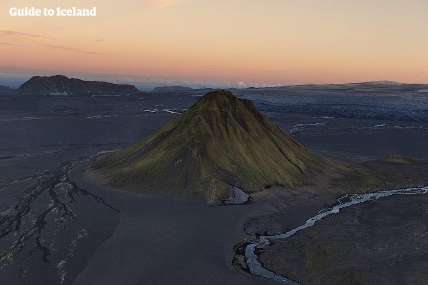 Ett fristående berg omgivet av svart sand i det isländska höglandet