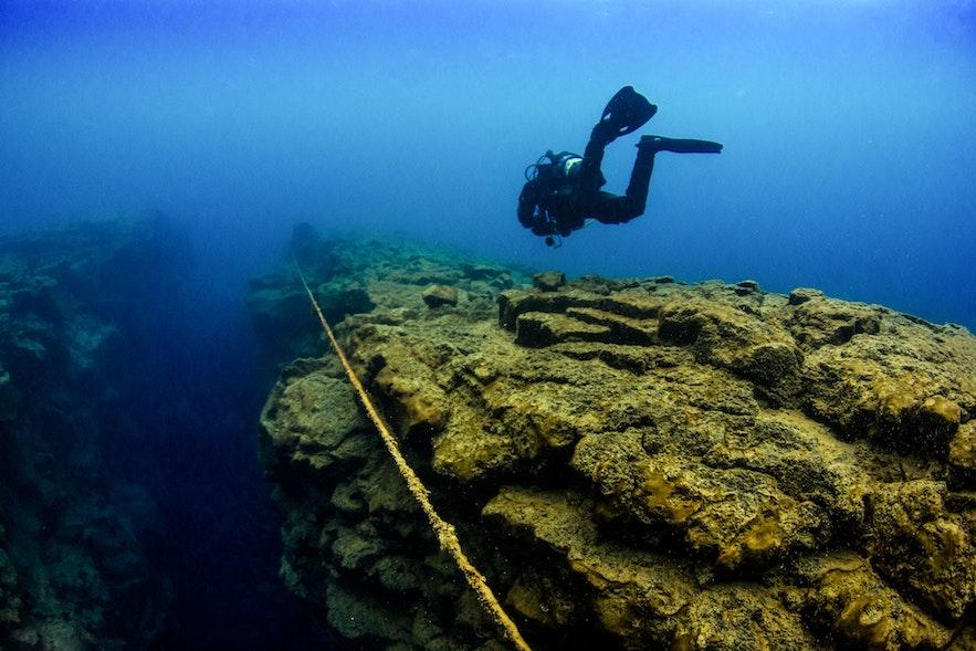 Un plongeur descend vers la faille de David en Islande
