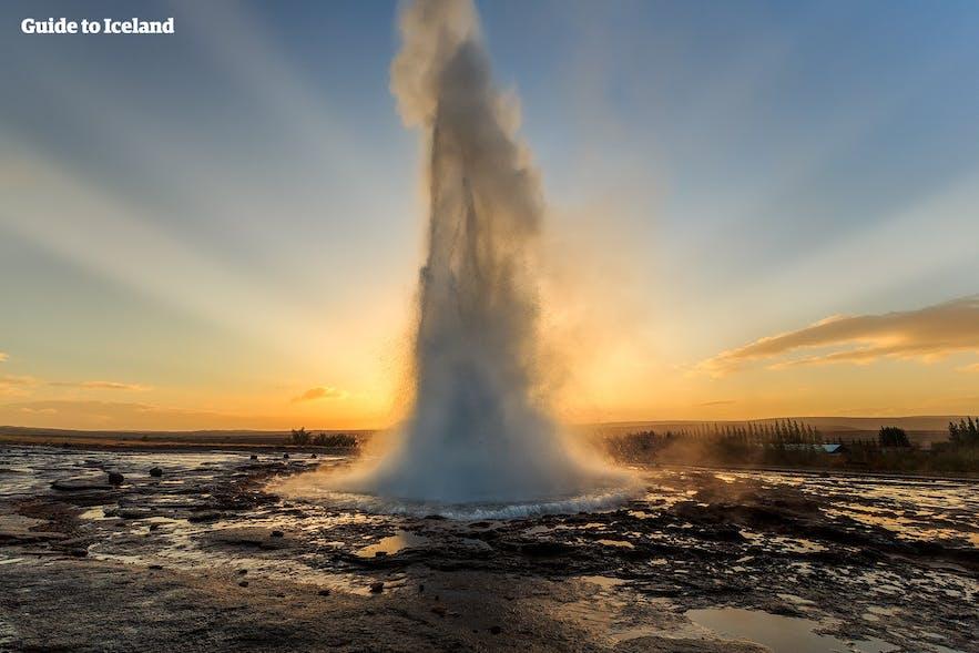 The geyser Strokkur erupting against the sun.