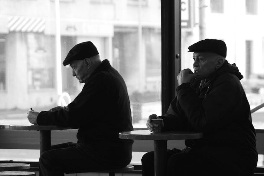 Dwóch dżentelmenów cieszących się ciepłą kawą na dworcu autobusowym Hlemmur.