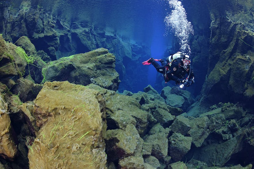 A scuba diver in the beautiful underwater world of Silfra.