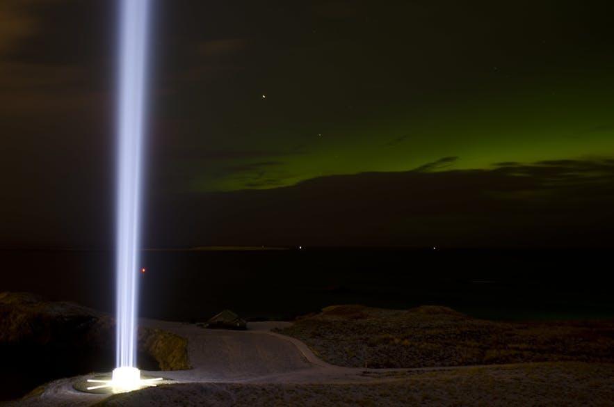 Der Imagine Peace Tower leuchtet vor der Kulisse des Nachthimmels.