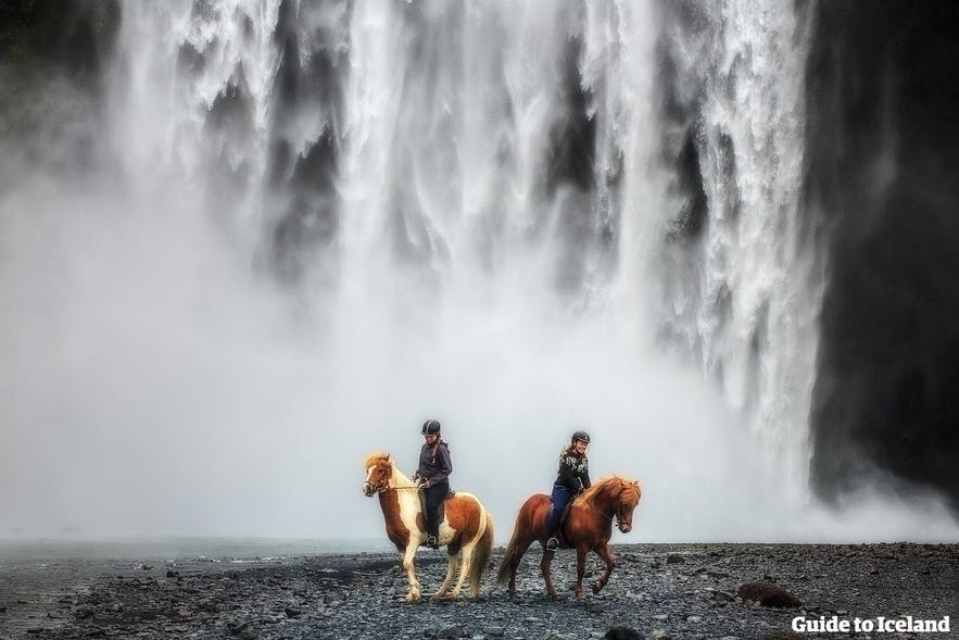 Riders in front of a waterfall on the south coast, leaving from Reykjavik, Iceland