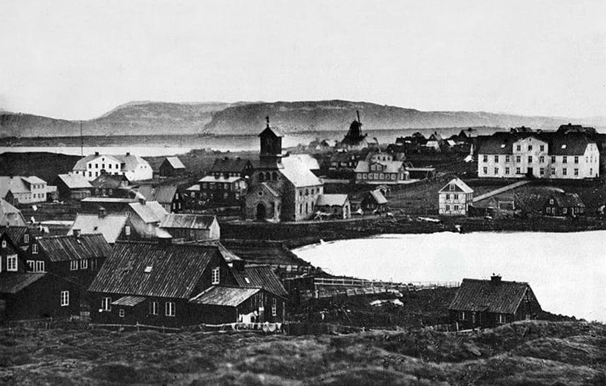 Reykjavik, around 1860. One can see how the lake stretches further than today, reaching all the way to Dómkirkjan cathedral. The large white building on the right is the old Reykjavik Mill, once a landmark, now no more.