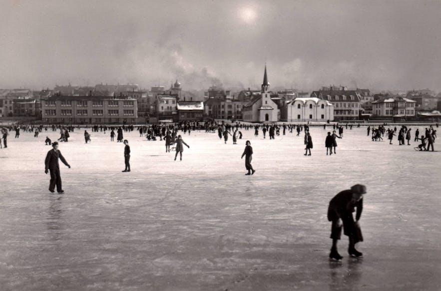 A historical photograph showing Reykjavik residents enjoying the frozen pond.