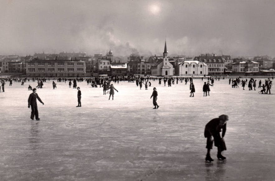 A historical photograph showing Reykjavik residents enjoying the frozen pond.