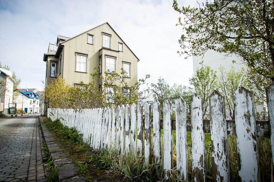 Białe ogrodzenia i wyłożone arkuszami blachy falistej fasady domów.