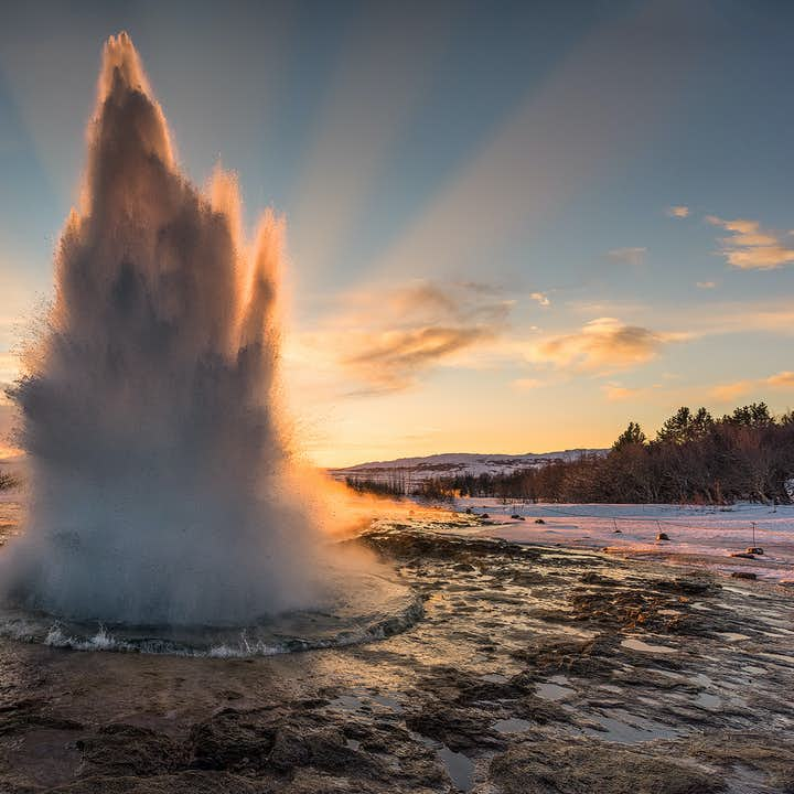 The moment Strokkur erupts, taken in winter at sunset.