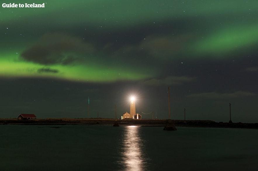 Zorza polarna nad latarnią morską, wybrzeże Islandii
