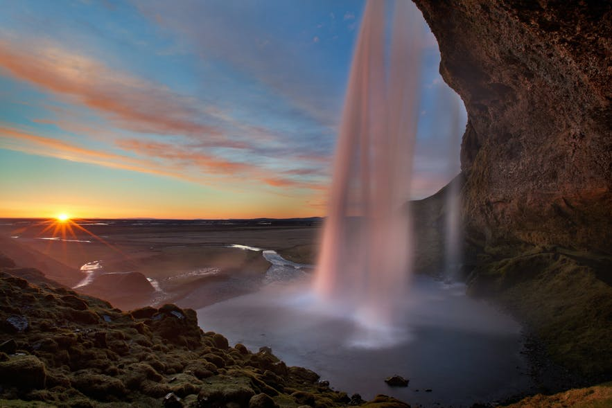 The view from behind the cascading water of Seljalandsfoss waterfall