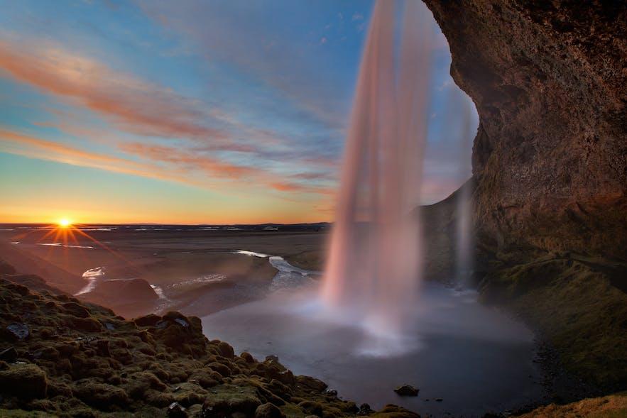 Blick von hinter dem herabstürzenden Wasser des Seljalandsfoss-Wasserfalls
