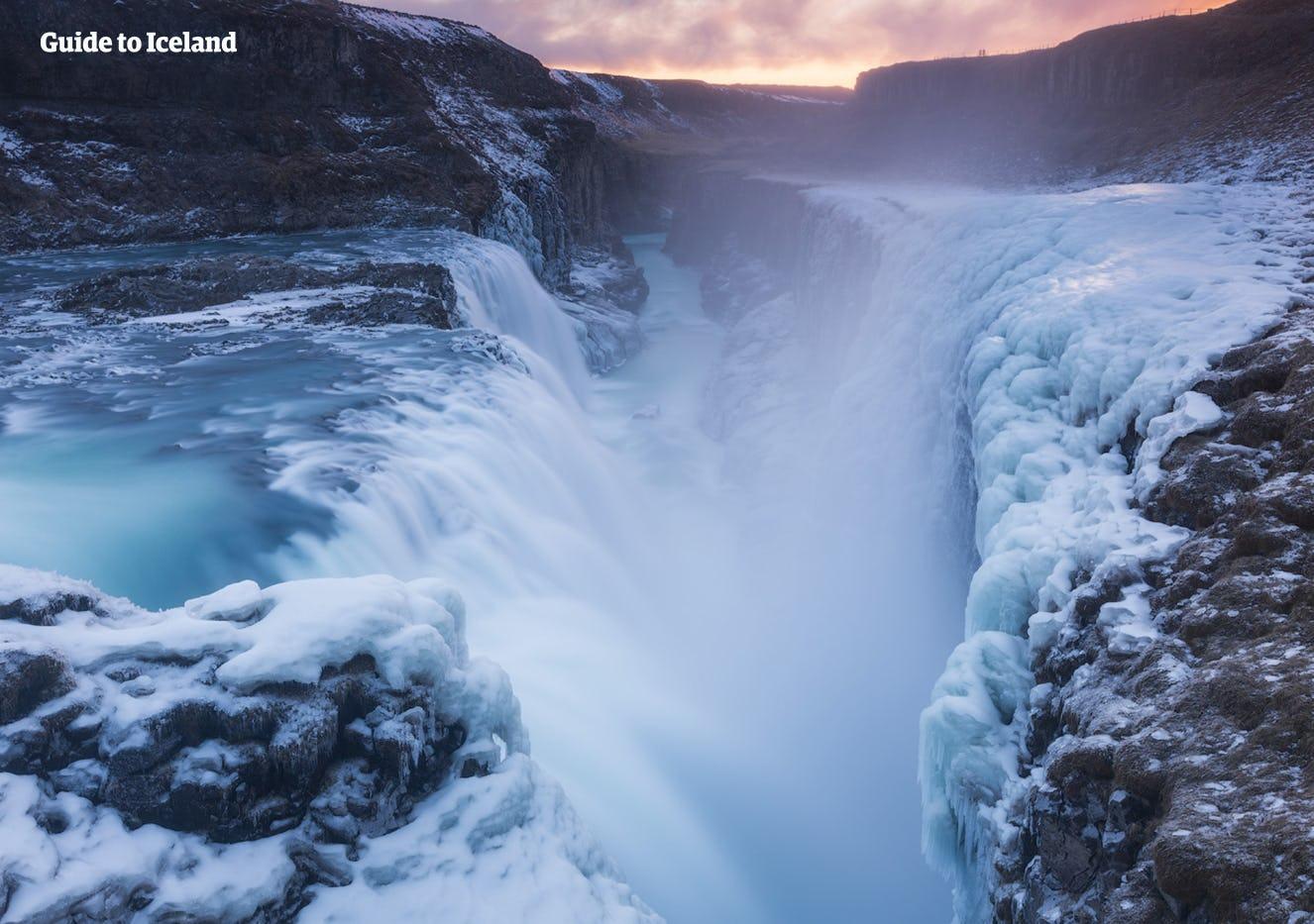 Chute d'eau de Gullfoss en hiver libérant des embruns glaciaux qui gèlent sur les roches et la mousse autour, créant une image dramatique de l'hiver.