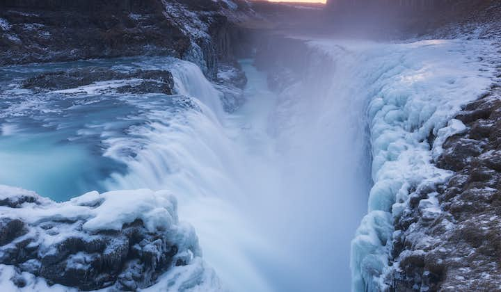 Gullfoss waterfall in winter releasing glacial spray that freezes on the rocks and moss around it, creating a dramatic winter image.