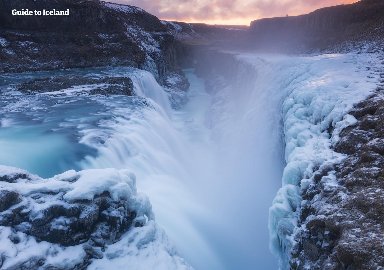 Wodospad Gullfoss zimą uwalniający lodowatą mgłę, która zamarza na skałach i mchu wokół niego, tworząc dramatyczny zimowy obraz.