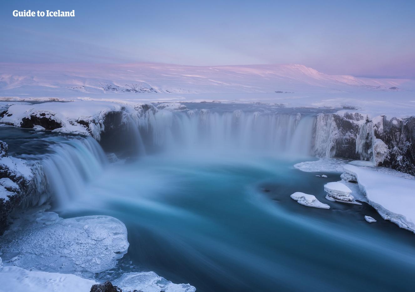 Bajo la luz rosada de un bajo sol invernal, la cascada Goðafoss continúa fluyendo a través de los paisajes nevados del norte de Islandia.