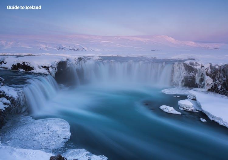 Plongée dans la lumière rose d'un faible soleil d'hiver, la cascade de Goðafoss combat les éléments gelés et continue de circuler dans les paysages enneigés du nord de l'Islande.
