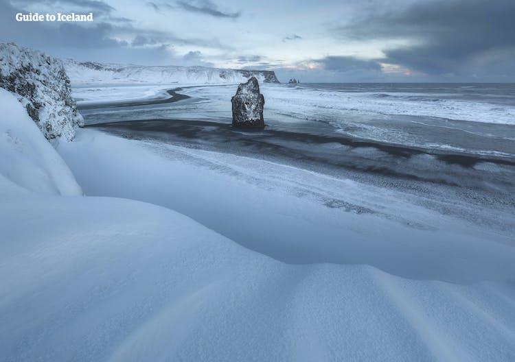 Czarne piaski plaż na południowym wybrzeżu Islandii podczas zimy są widoczne tylko tam, gdzie morze zmywa śnieg.