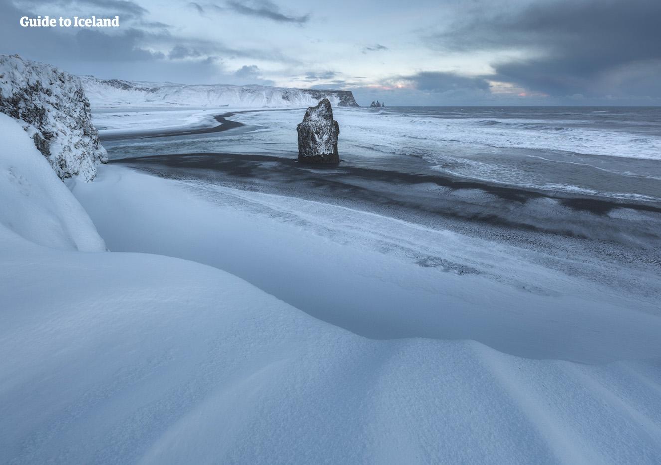 Les sables noirs des plages de la côte sud de l'Islande dans les profondeurs de l'hiver ne sont visibles que là où la mer enlève la neige.