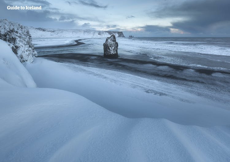 The black sands of Iceland's South Coast beaches in the depths of winter are only visible where the sea washes away the snow.