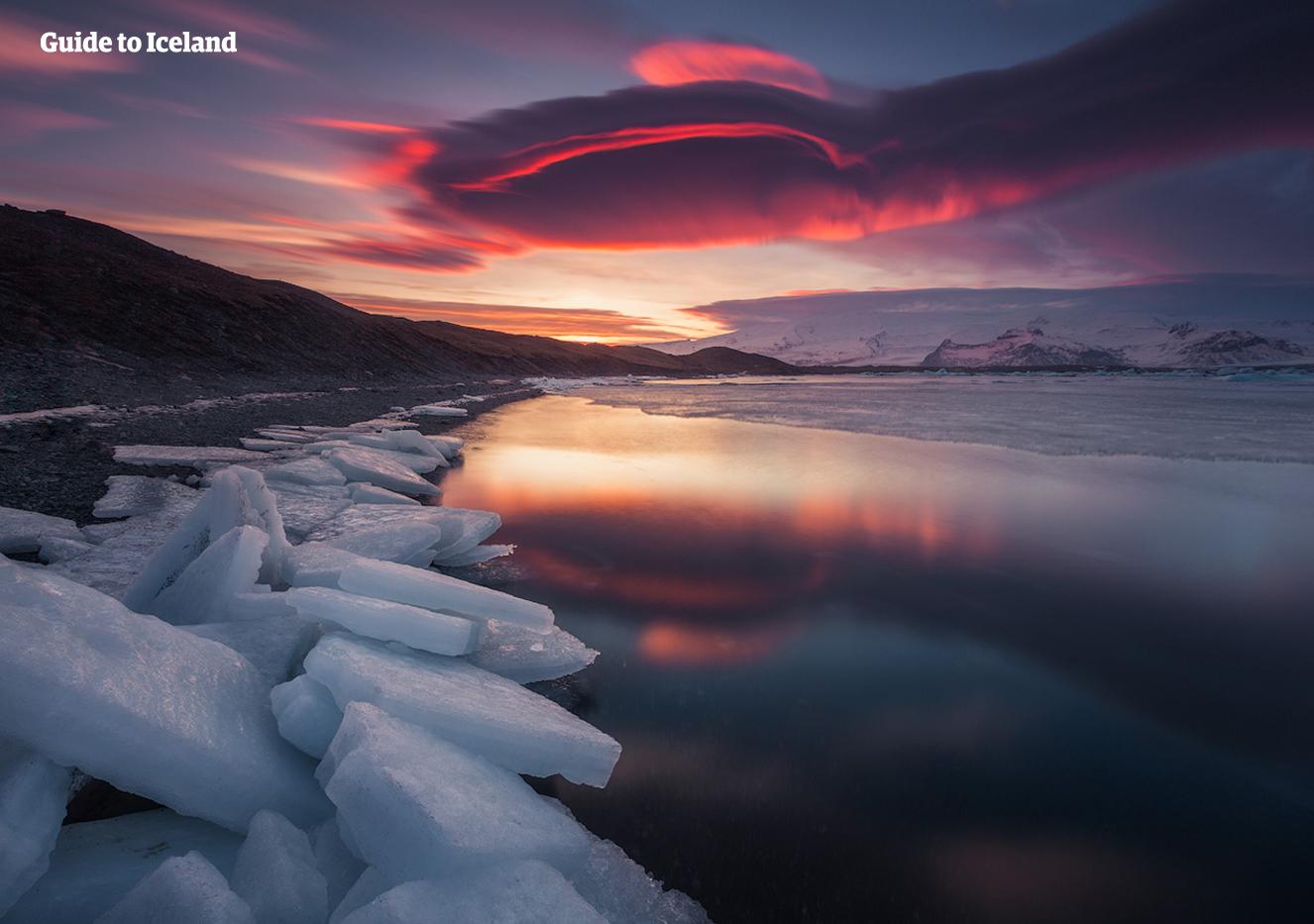 Den røde kveldshimmelen gjenspeilet i den rolige bresjøen Jökulsárlón.