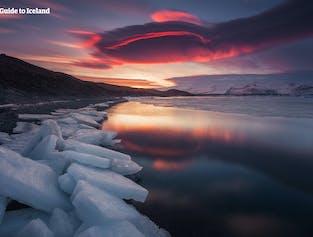 Der rote Abendhimmel spiegelt sich in der stillen Gletscherlagune Jökulsárlón.