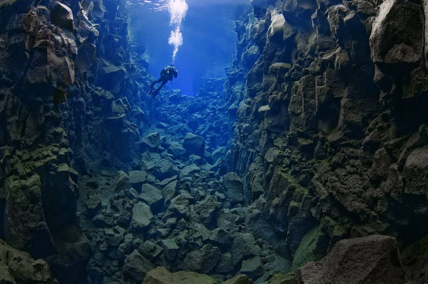 """A diver swimming through Silfra's middle section, """"The Hall."""""""
