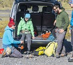 Hikers getting ready to conquer a glacier in Iceland, attaching crampons to their shoes.
