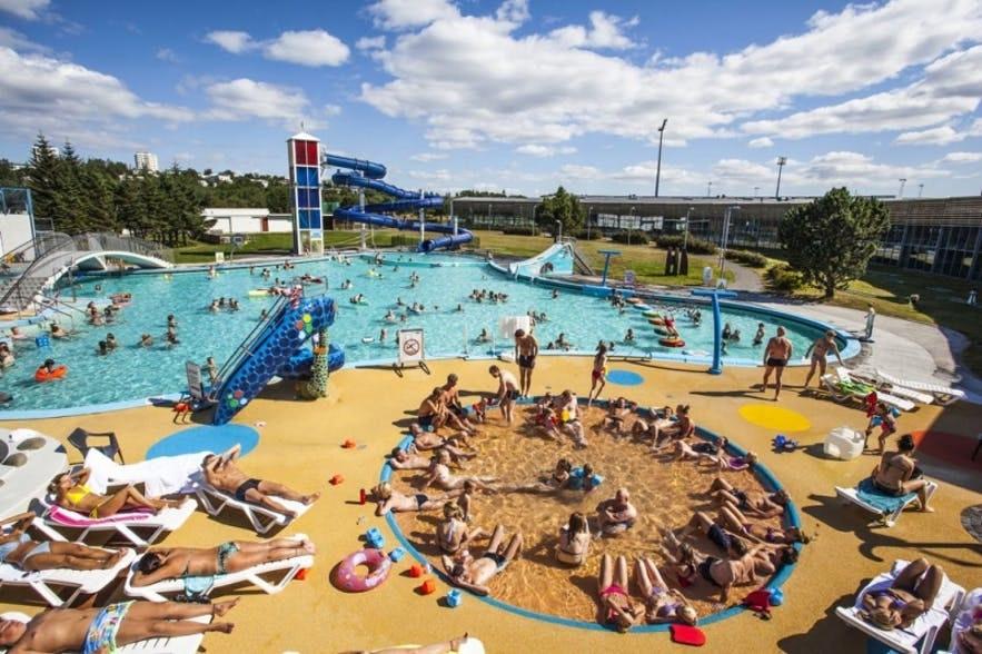Solskinsdag i Laugardalslaugs geotermiske svømmebassiner