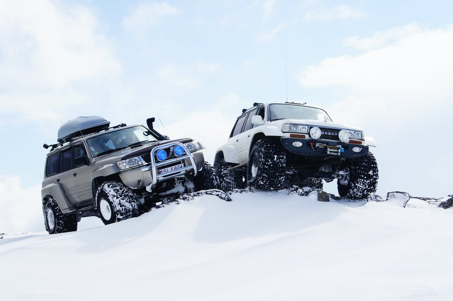Two super jeeps on the crest of a snowy hill