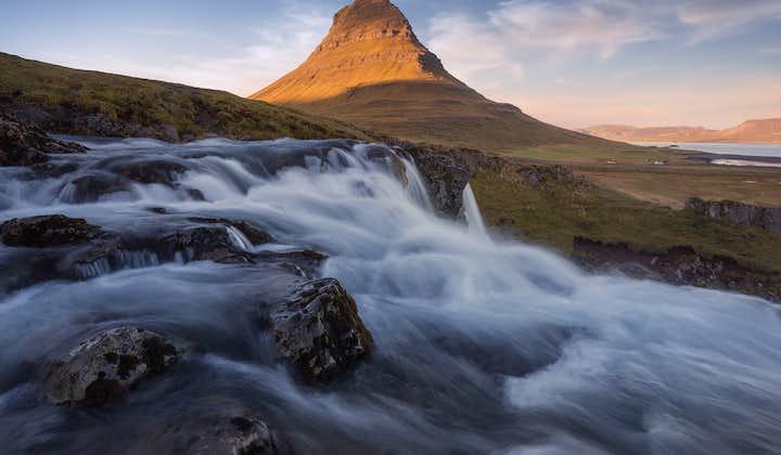 The waterfall Kirkjufellsfoss, on the Snæfellsnes Peninsula, surges in the foreground of the iconic peak, Kirkjufell.