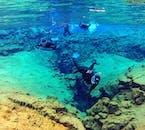 un plongeur masque et tuba plongeant au fond de Silfra en combinaison humide