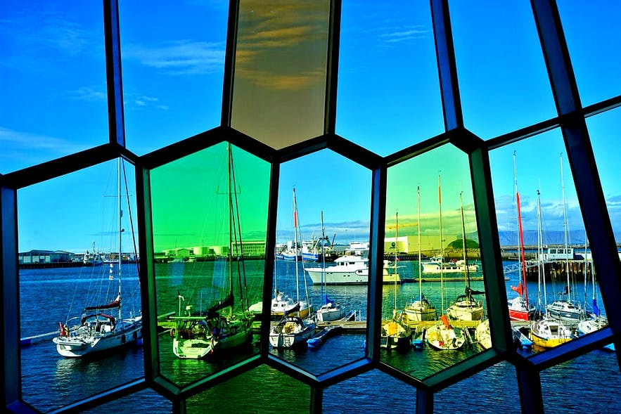 A view of the boats of Reykjavík's Old Harbour through Harpa's colourful glass panels