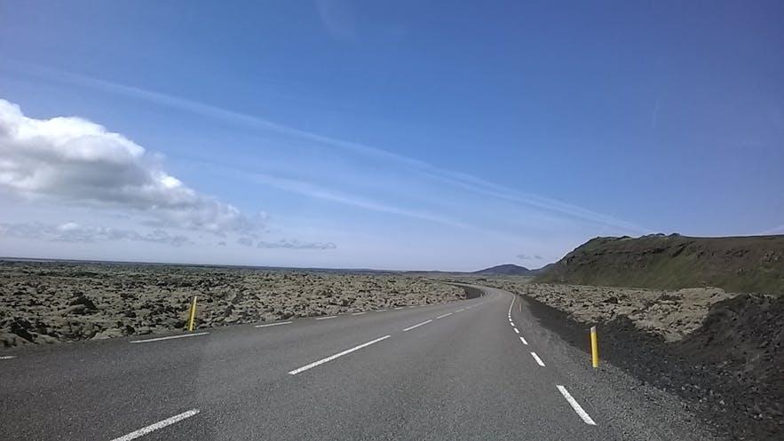 A road cuts through the moss-coated Ögmundarhraun lava field.
