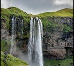 The high and narrow Seljalandsfoss waterfall, cascading over a cave, carved by nature into the cliff face