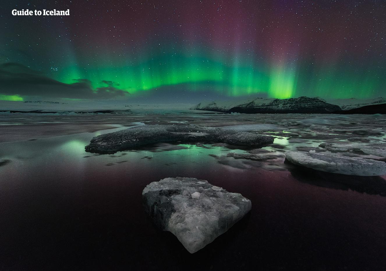 ヨークルスアゥルロゥン氷河湖の上空に現れたオーロラはピンク、緑、紫とさまざまな色をしている