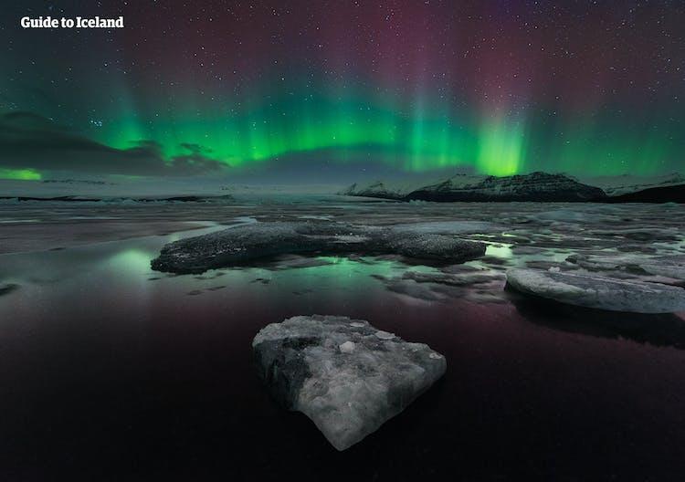 แสงสีเขียว ชมพู และม่วงของแสงเหนือขณะที่เต้นรำอยู่บนทะเลสาบน้ำแข็งโจกุลซาลอน