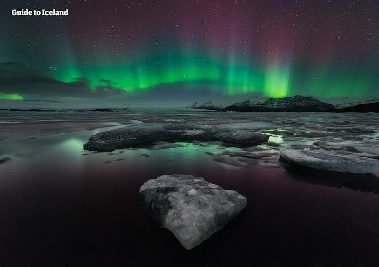 I colori verde, rosa e viola dell'aurora boreale, sopra la laguna glaciale di Jökulsárlón