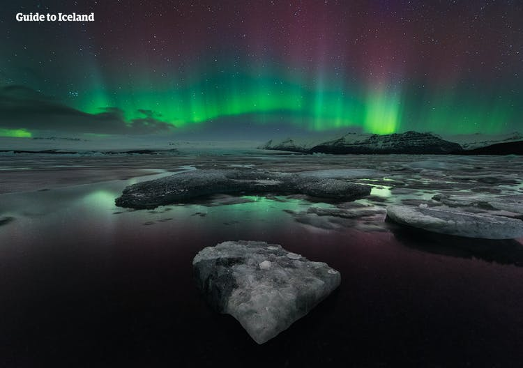 The green, pink and purple colours of the Northern Lights as they dance above Jökulsárlón glacier lagoon