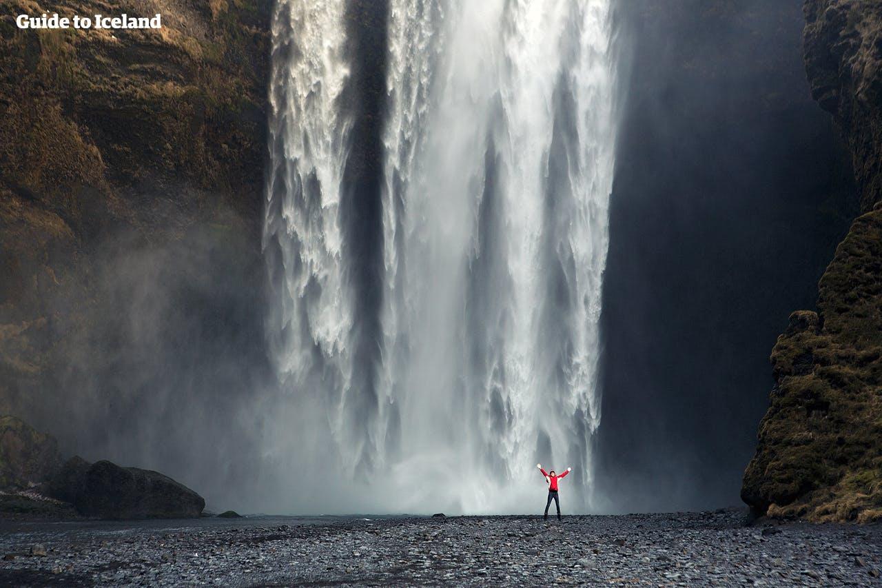 Ziemia pod wodospadem Skógafoss na południowym wybrzeżu jest bardzo płaska, więc możesz podejść do ściany wody.