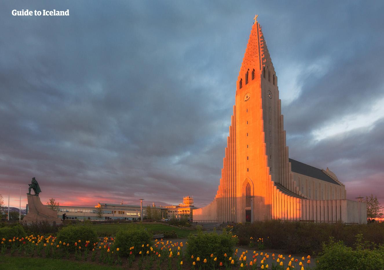 Den majestätiska Hallgrímskirkja-kyrkan i Reykjavík som inramas av midnattssolens varma glöd