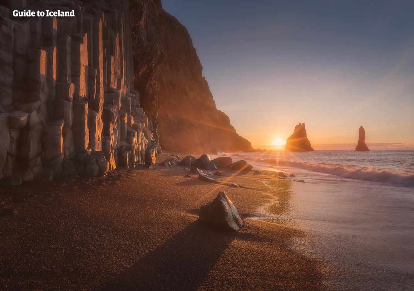 Słońce świeci na czarnej, piaszczystej plaży Reynisfjara, otoczonej klifami sześciokątnych bazaltowych kolumn.