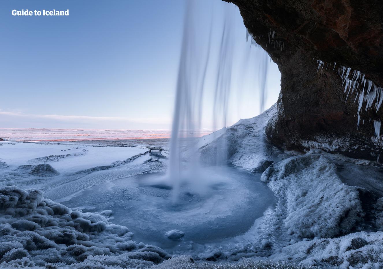 Mroźny widok zza kaskadowej wody przy wodospadzie Seljalandsfoss na południowym wybrzeżu Islandii.